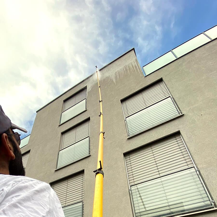 Simplex Anwendungstechniker reinigt Fassade mit der Lanze