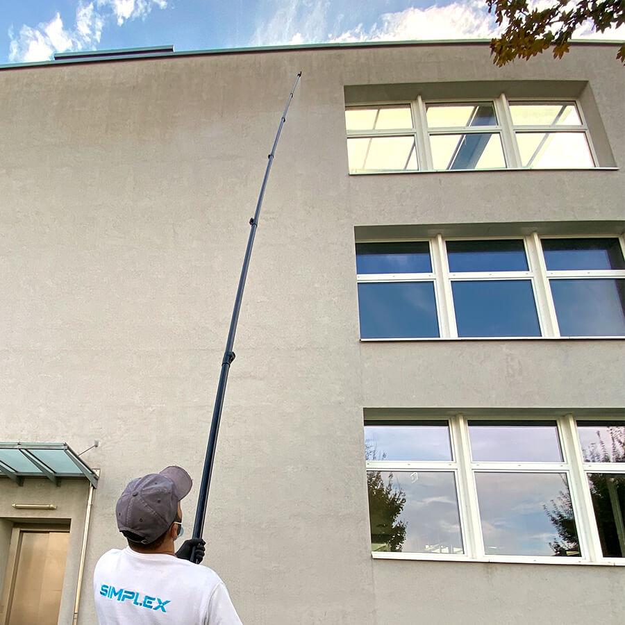 Simplex Anwendungstechniker sprüht Vorbehandlung auf Fassade