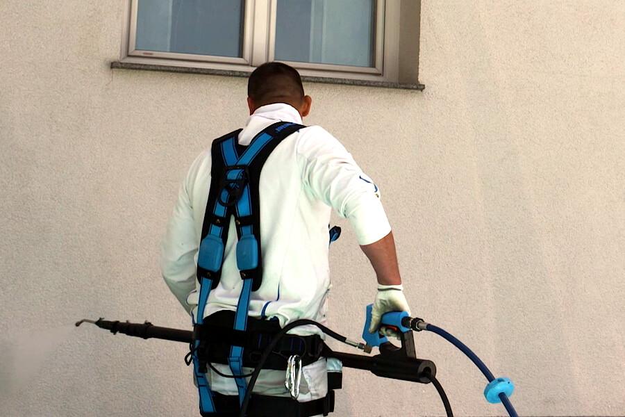 Mann mit Lanze reinigt Fassade